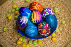 Голубая плита с пестроткаными пасхальными яйцами, конфетами, предпосылкой соломы Стоковое Изображение RF