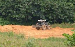 Голубая работа tracktor на поле Стоковая Фотография