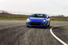 Голубая спортивная машина на пути гонки стоковое фото rf