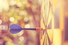 Голубая стрелка дротика в центре dartboard Нерезкость и bokeh Стоковое Изображение RF