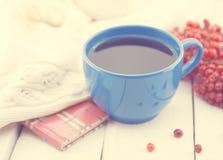 Голубая чашка терапевтического травяного чая с ягодой рябины на белом деревенском деревянном столе альтернативный bamboo поднос с Стоковое фото RF