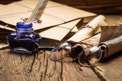 Голубая чернильница и стекла окруженные старыми сообщениями и enve стоковые фотографии rf