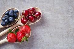 Голубика, вишня и клубника в деревянных ложках, сверху Стоковое Фото