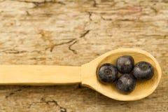 Голубики в ложке на деревянной предпосылке, конце-вверх Стоковые Фото