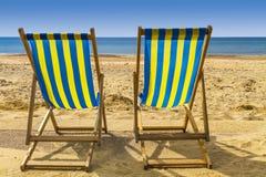 2 голубое и желтые deckchairs смотря на море через золотой песок Стоковое Фото