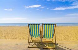 2 голубое и желтые deckchairs смотря на море через золотой песок Стоковые Фотографии RF