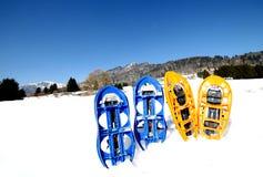 4 голубое и оранжевые snowshoes в горах Стоковое Изображение