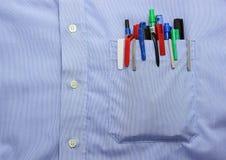 Голубое карманн рубашки с много различные ручка и дн шариковой авторучки Стоковое Фото