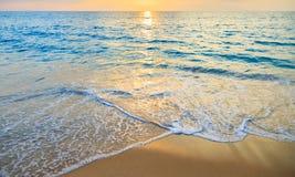 Голубое море и золотой песок с предпосылкой захода солнца Стоковое Изображение