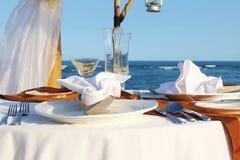 Голубое море и таблица для романтичного обедающего на beac Стоковые Изображения