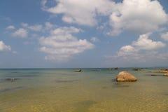 Голубое море с камни и небо с белыми облаками стоковое изображение