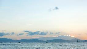 Голубое небо, белые облака, море береговой линии на заходе солнца Стоковые Изображения