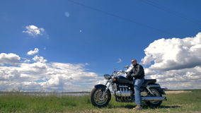 Голубое небо и белые облака, велосипедист и его мотоцикл видеоматериал