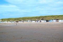 Голубое небо, пляжные домики и зеленые дюны Стоковые Фото