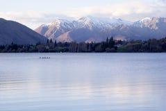 Голубое озеро с лесом и снегом покрыло горы Стоковое Изображение RF
