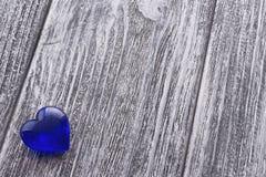 Голубое сердце на сером цвете покрасило деревянную предпосылку Стоковая Фотография