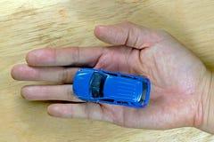 Голубой автомобиль игрушки в мужской руке над деревянным столом для концепции перемещения Стоковые Изображения RF