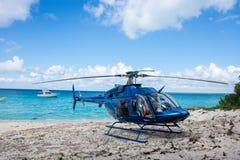 Голубой вертолет на пляже на дереве и красивом океане и облаках на backgorund Стоковое фото RF
