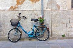 Голубой велосипед против внешней стены стоковое изображение