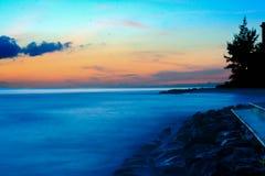 Голубой и розовый туманный заход солнца пляжа Стоковые Фото