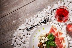 Голубой сыр, сырцовое hamon, базилик, гайки и одиночное стекло красного вина на белом камне и на деревянной предпосылке, взгляд с Стоковые Изображения RF