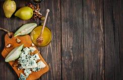 Голубой сыр с медом, оливкой и грушами на деревенской таблице Место текста Стоковое Изображение