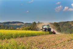 Голубой трактор в поле мустарда в чехии Пылевоздушные поле и сельскохозяйственные работы Работы по дому фермы осени Стоковые Фото