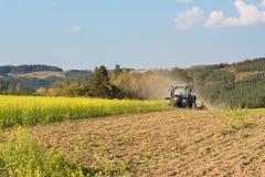 Голубой трактор в поле мустарда в чехии Пылевоздушные поле и сельскохозяйственные работы Работы по дому фермы осени Стоковое Фото