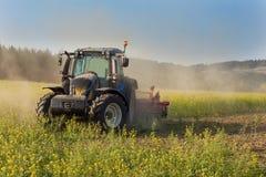 Голубой трактор в поле мустарда в чехии Пылевоздушные поле и сельскохозяйственные работы Работы по дому фермы осени Стоковая Фотография