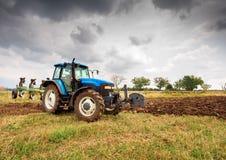 Голубой трактор и драматическое небо Стоковые Изображения
