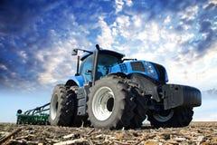 Голубой трактор работая на ферме Стоковое Фото