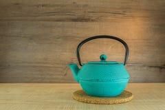 Голубой чайник чугуна на деревянной предпосылке Стоковые Фото