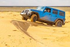 Голубой Wrangler Rubicon виллиса неограниченное на песчанных дюнах пустыни Стоковые Фотографии RF