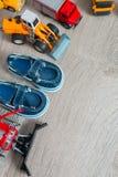 Голубые ботинки шлюпки для мальчика близко установили игрушки автомобиля на серой деревянной предпосылке Взгляд сверху Рамка скоп Стоковое фото RF