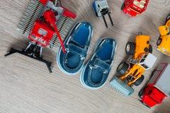 Голубые ботинки шлюпки для мальчика близко установили игрушки автомобиля на серой деревянной предпосылке Взгляд сверху Рамка скоп Стоковое Изображение RF