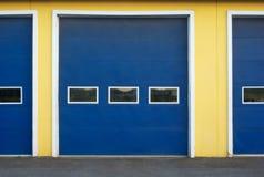 Голубые двери гаража на здании желтой стены коммерчески Стоковые Фотографии RF
