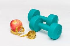 Голубые гантели, красное яблоко, лента на белой предпосылке Стоковое Изображение RF