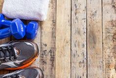Голубые гантели, полотенце и ботинки спорт на деревянном столе Стоковое фото RF