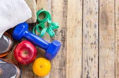 Голубые гантели, полотенце и ботинки спорт на деревянном столе Стоковые Фото