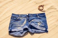 Голубые джинсы замыкают накоротко на песке Стоковое Изображение