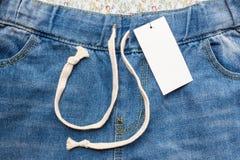 Голубые джинсы моды и бирка ярлыка Стоковые Изображения RF