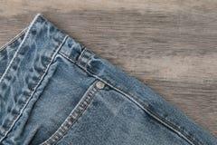 Голубые джинсы на коричневой деревянной предпосылке стоковое изображение