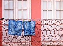 Голубые джинсы на розовом окне Стоковое фото RF