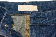 Голубые джинсы с белым ярлыком ткани Стоковое фото RF