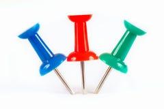 Голубые, зеленые и красные pushpins вставили в белой бумаге Стоковое Фото