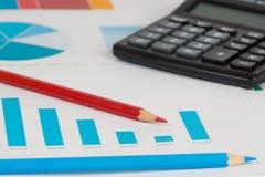 Голубые диаграммы в виде вертикальных полос с калькулятором и карандашами 1 Стоковое Изображение