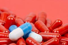 Голубые и белые пилюльки на предпосылке красных пилюлек Стоковая Фотография RF