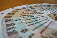 Голубые и коричневые бумажные деньги в значении 50 и 100 русских рублей формируя форму круга Стоковая Фотография RF