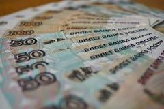 Голубые и коричневые бумажные деньги в значении 50 и 100 русских рублей формируя форму круга Стоковые Фото