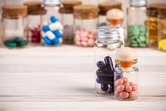 Голубые капсулы и розовые пилюльки в фронте Стоковая Фотография